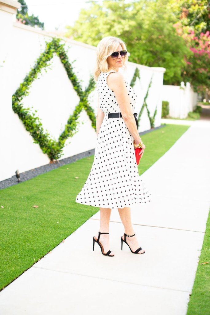 Twirling into Fall in Harper Rose midi dress   3 Things to Look for in a Polka Dot Midi Dress by popular Dallas fashion blogger, Tanya Foster: image of a woman standing outside by a white wall and wearing a Nordstrom Harper Rose Polka Dot Fit & Flare Dress, black stiletto heel sandals, sunglasses, and holding a red clutch.