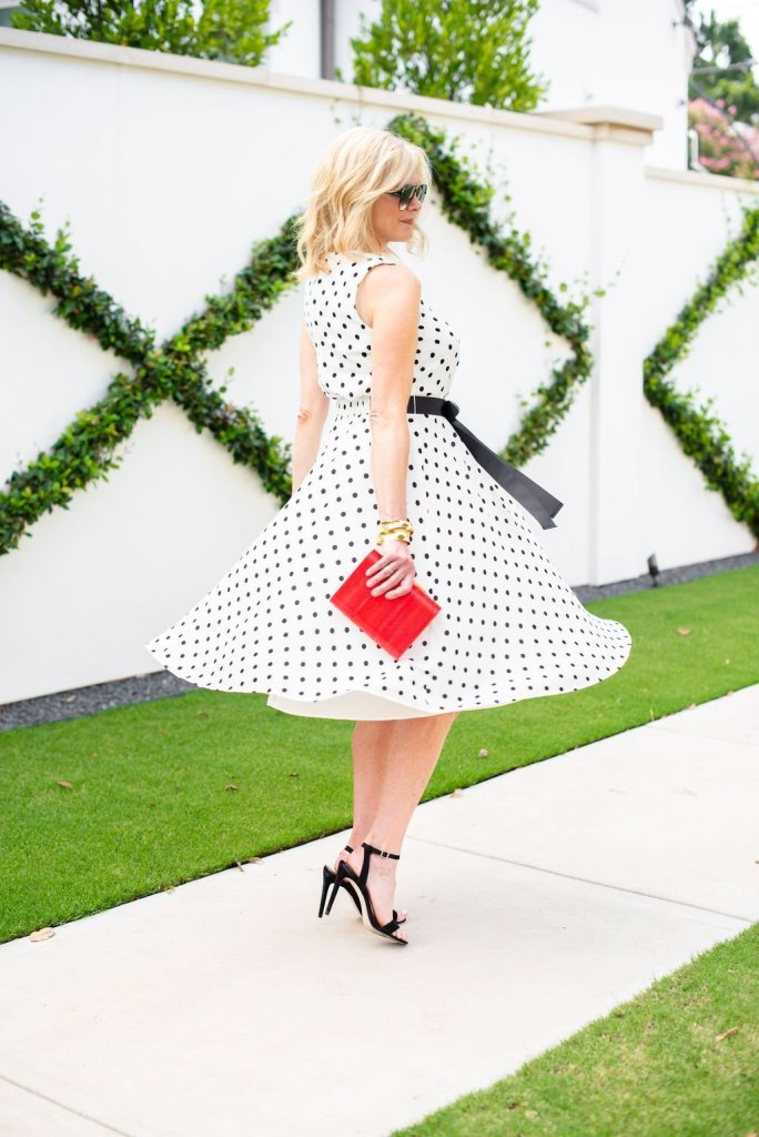 Twirling into Fall in Harper Rose midi dress | 3 Things to Look for in a Polka Dot Midi Dress by popular Dallas fashion blogger, Tanya Foster: image of a woman twirling outside by a white wall and wearing a Nordstrom Harper Rose Polka Dot Fit & Flare Dress, black stiletto heel sandals, sunglasses, and holding a red clutch.
