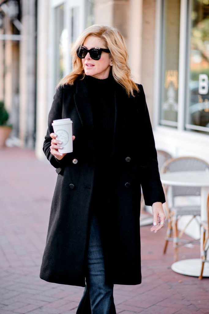 tanya foster holding coffee wearing black chico's turtleneck mango black wool coat frame denim jeans and animal print booties