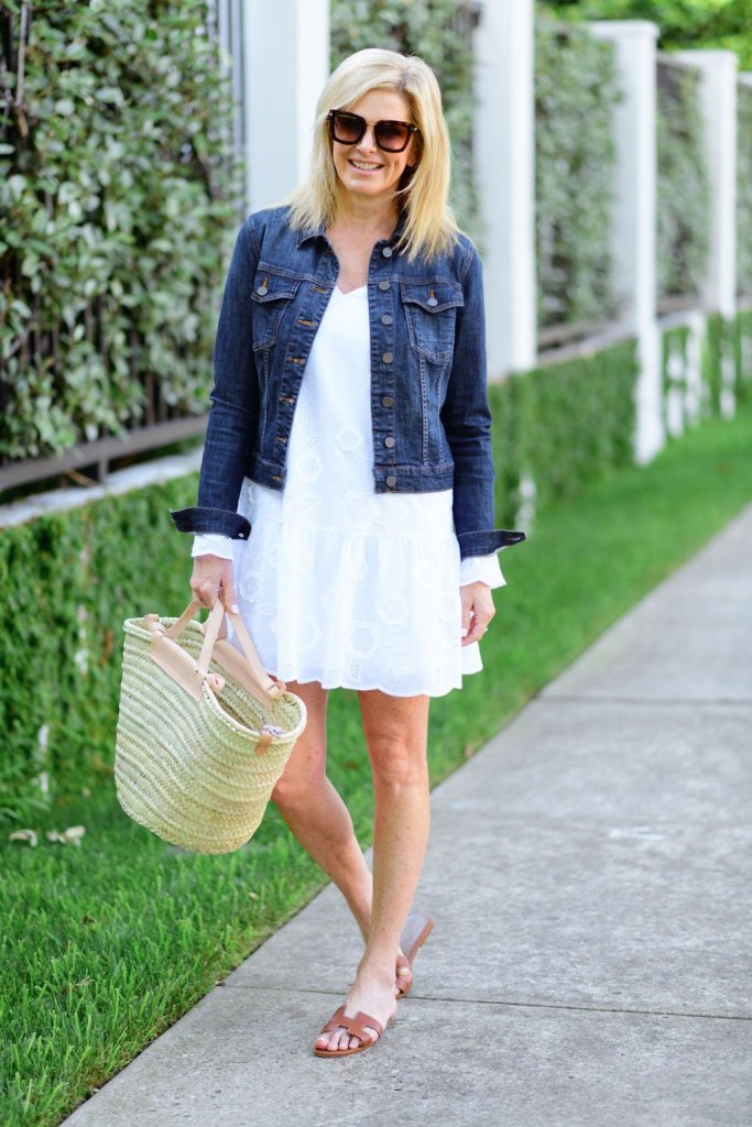Tanya Foster in white sail to sable dress with hermes oran sandals and mango straw bag and jean jacket