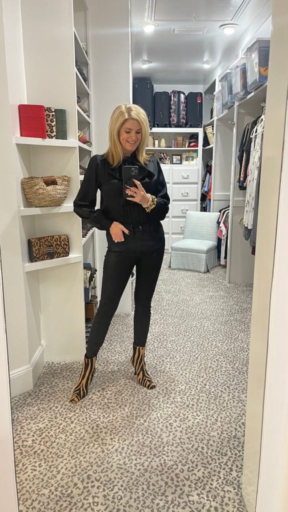 tanya foster in black silk bow blouse good american coated skinny jeans and leather mango boots