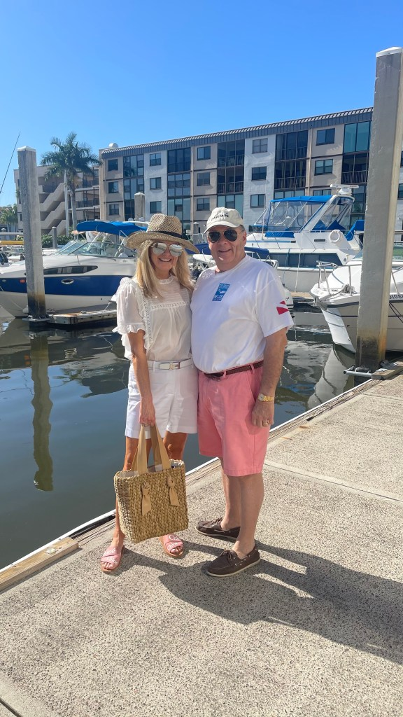 tanya foster in front of boat dock with husband tanya foster wearing talbots girlfriend denim shorts while blouse, avara hat and chloe slide sandals and pamela munson bag