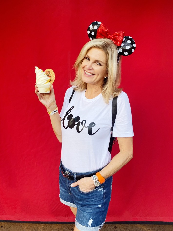 Tanya Foster in a minnie ears and disney shirt holding a dole whip