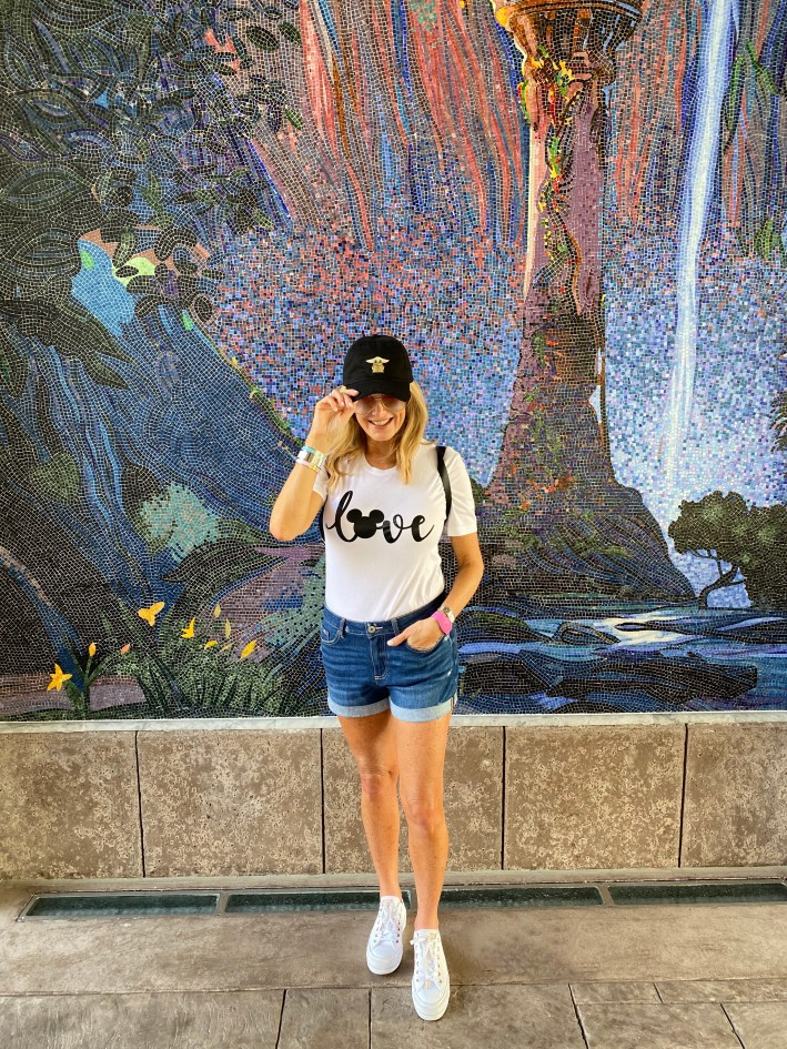 Tanya Foster standing in front of a mural at walt disney world in disney clothing and hat