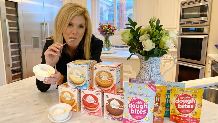 Tanya Foster sitting with enlightened cheesecake pack and cookie dough bites product roundup