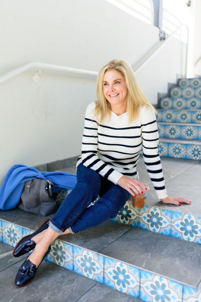 Tanya Foster sitting on steps in Talbots sweater, jeans and mules
