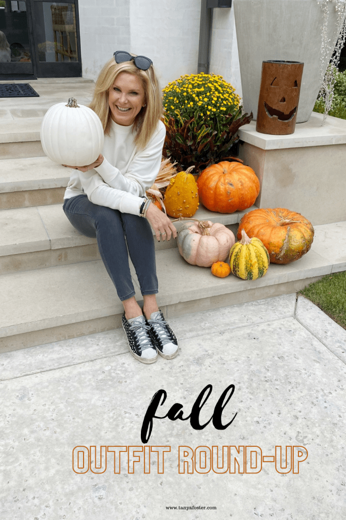 Tanya foster sitting with a pumpkin wearing Mott&bow gray skinny jeans and crewneck sweatshirt with p448 sneakers