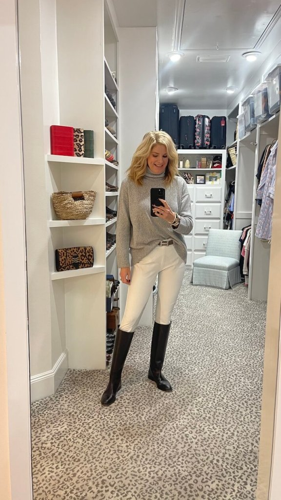 tanya foster in gray turtleneck sweater, white riding pants and black riding boots