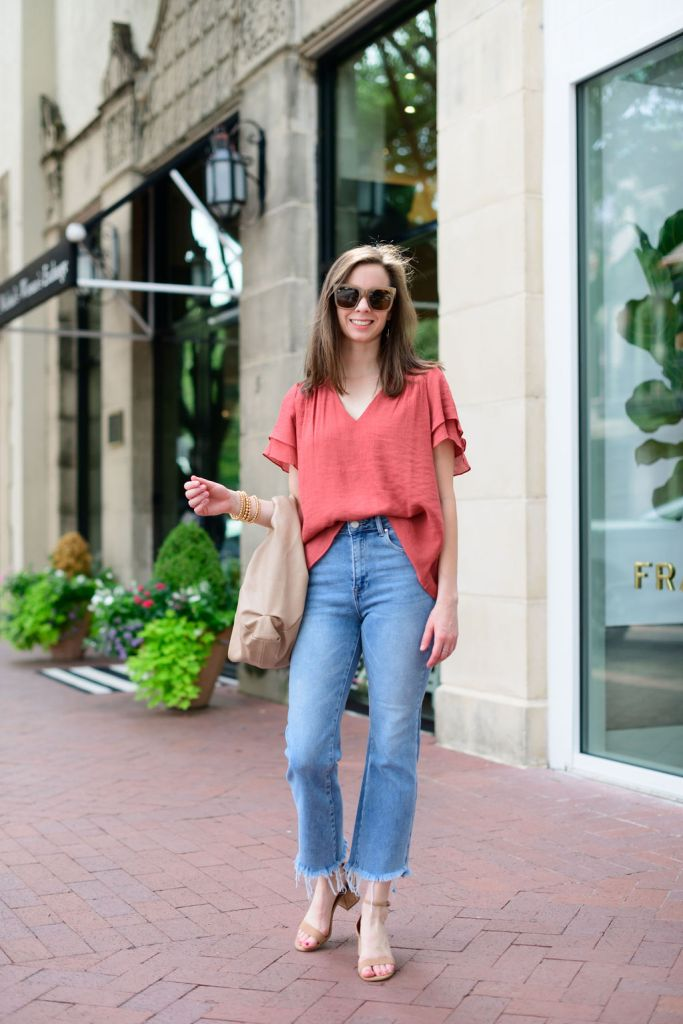Woman wearing avara rust blouse and jeans