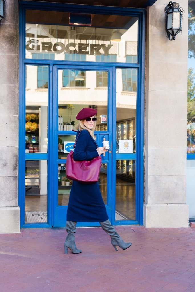 tanya foster walking in a sweater dress and boots with a beret and bag
