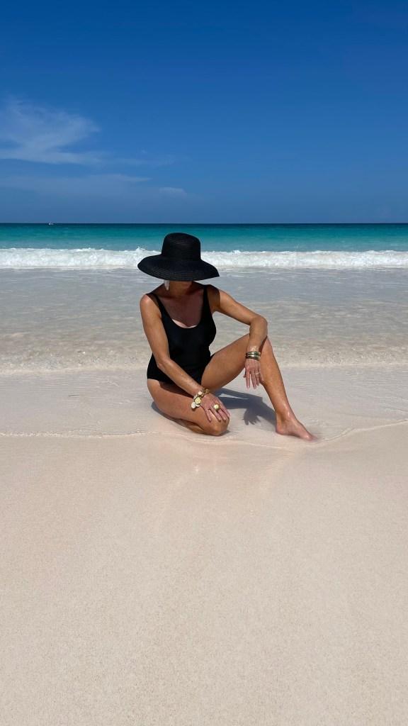 Tanya Foster wearing black swimsuit and black avara straw hat