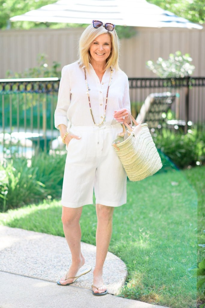 Tanya Foster in white linen blouse and shorts from chicos with mango straw bag