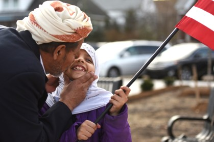 Ngi Pedy, of Hamtramck, kisses Zohowr Almasmirari, 8, on the check as she holds an American flag at a rally against terrorism in Hamtramck, Mich. Friday afternoon Dec. 11, 2015. (Tanya Moutzalias | MLive Detroit)