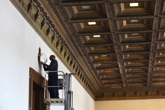 A worker at the Detroit Public Library's main branch sets the clock one hour forward ahead of day lights savings which 'springs forward' at 2 a.m. Sunday, March 7, 2015. (Tanya Moutzalias | MLive Detroit)