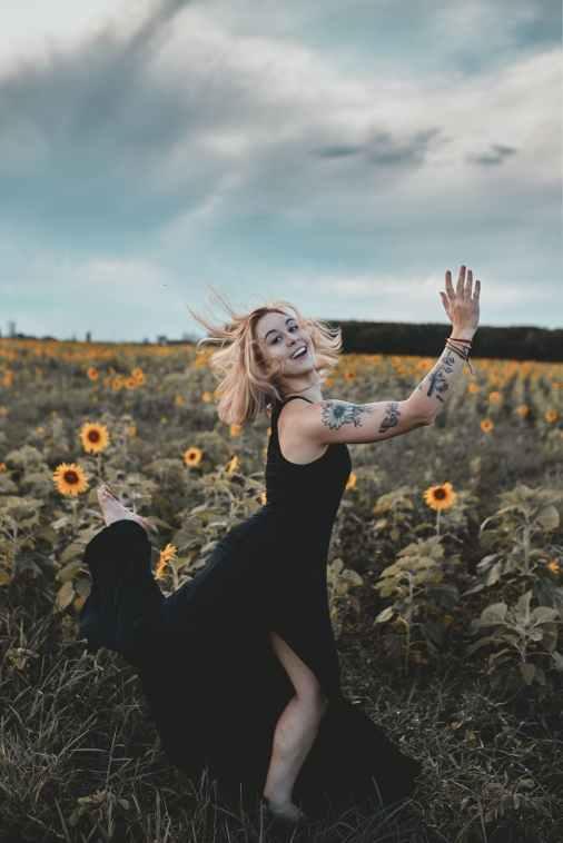 woman in black dress standing on sunflower field