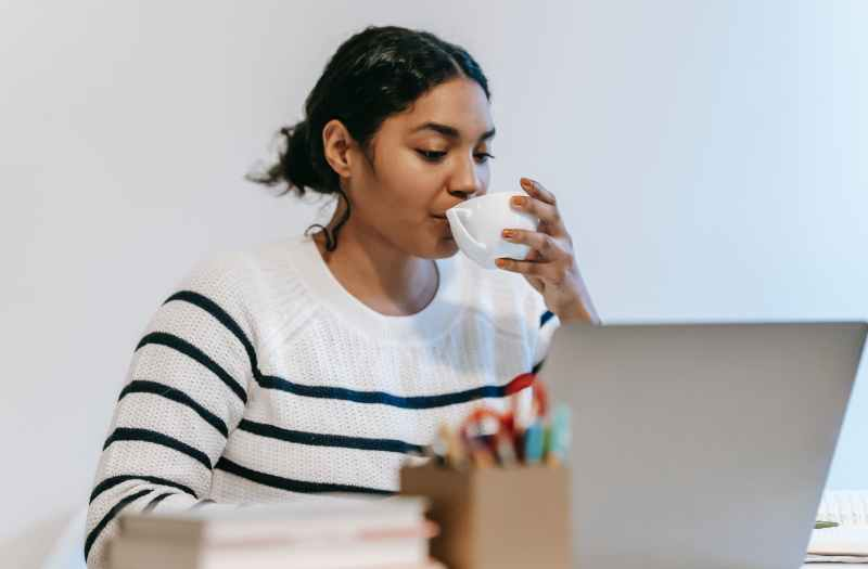 ethnic lady working remotely on laptop with cup of drink