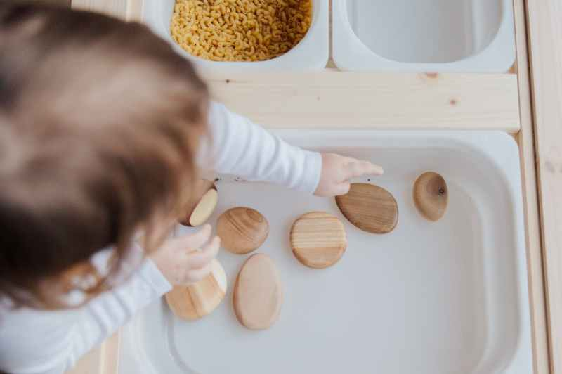 crop anonymous child getting brown stones from white container at home