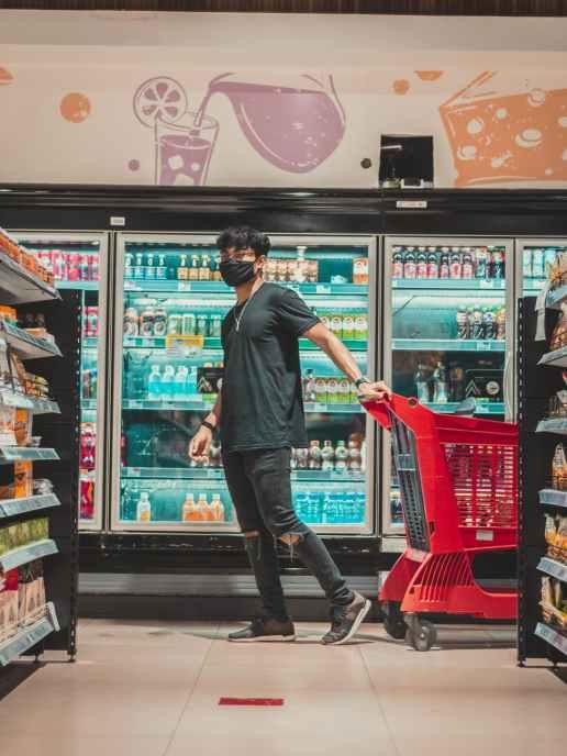 man with trolley walking near fridge in supermarket