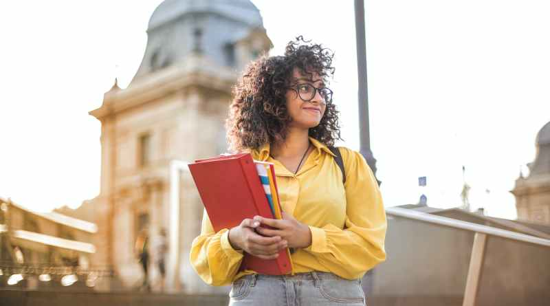 woman in yellow jacket holding books