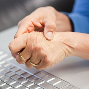A person rubbing painful hands. Arthritis.