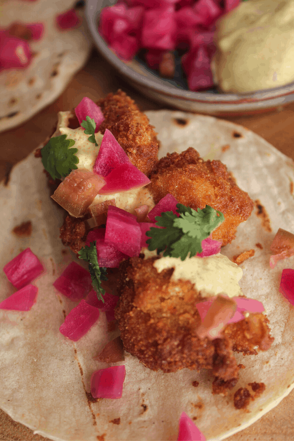 Curried cauliflower taco up close with bowl of condiments in background