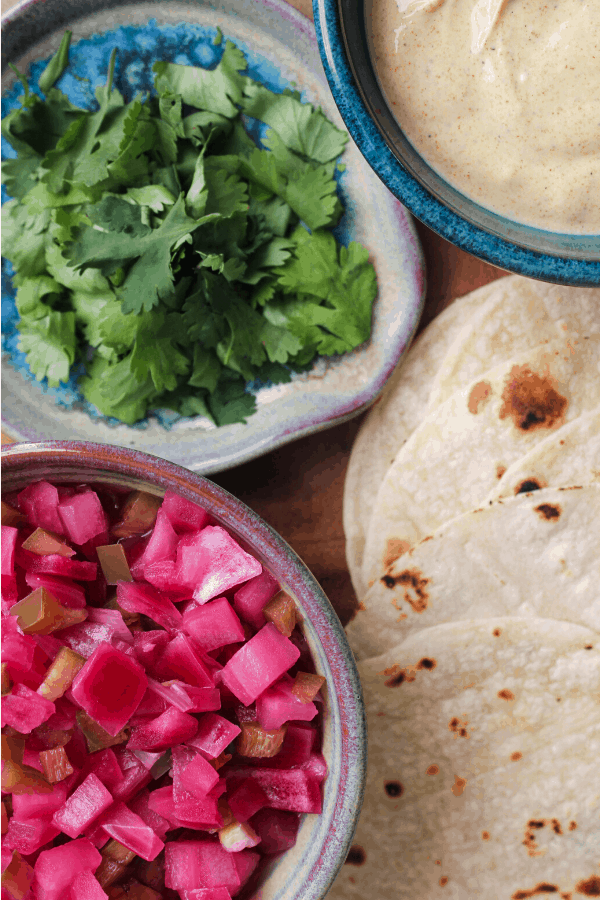 cilantro, curry yogurt sauce and red onions in small bowls with corn tortillas.