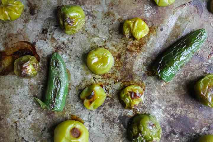 roasted tomatillos and jalapenos on baking sheet