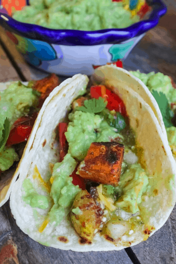 Close up of roasted vegetable tacos with small bowl of mashed avocado.