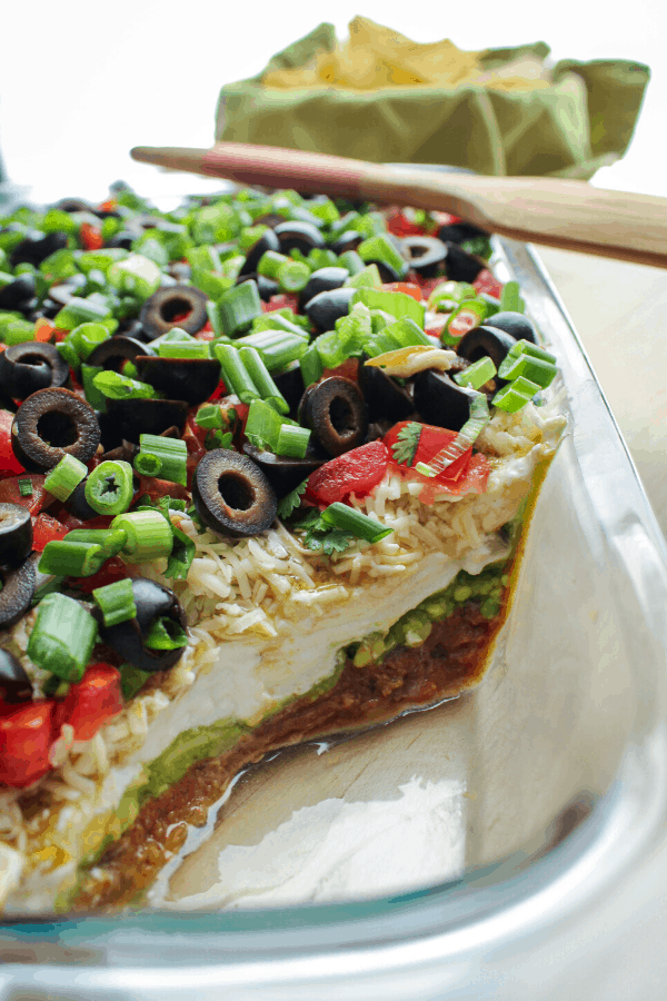 spicy 7 layer dip in a glass baking dish with wood spatula across and basket of chips in background