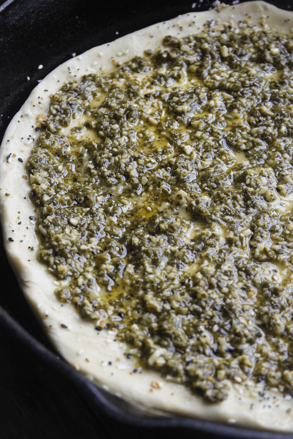 Pesto covered dough for breakfast BLT cast-iron pizza.