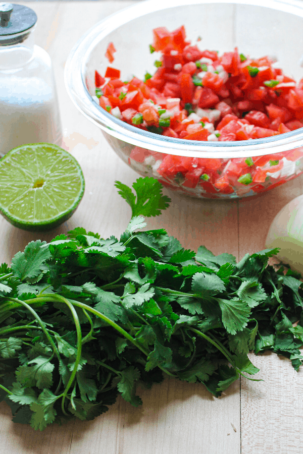 bowl of diced tomato, onion, and jalapeno on wood surface with jar of salt, half of a lime, half a white onion, and a bunch of cilantro.