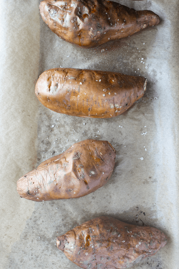 four baked sweet potatoes on parchment paper lined baking sheet