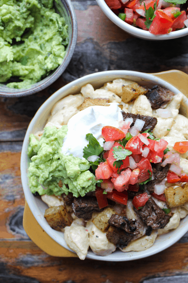 carne asada fries mac & cheese in bowl with side of guacamole in bowl an side of pico de gallo in bowl on wood surface