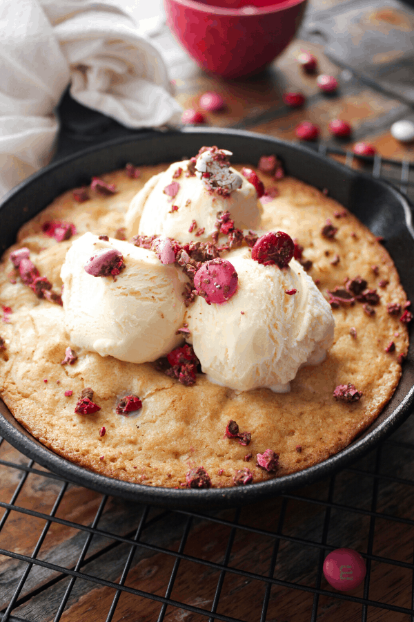 Blondie in a cast-iron skillet topped with three scoops of ice cream and crushed M&M's.