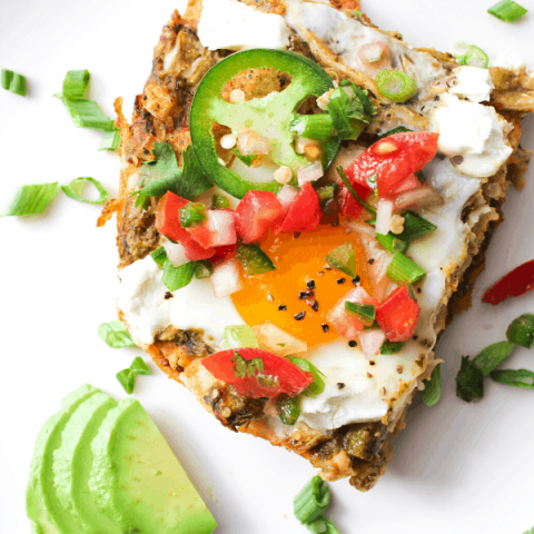 close up shot of slice of huevos rancheros casserole covered in pico on white surface with slices of avocado from above