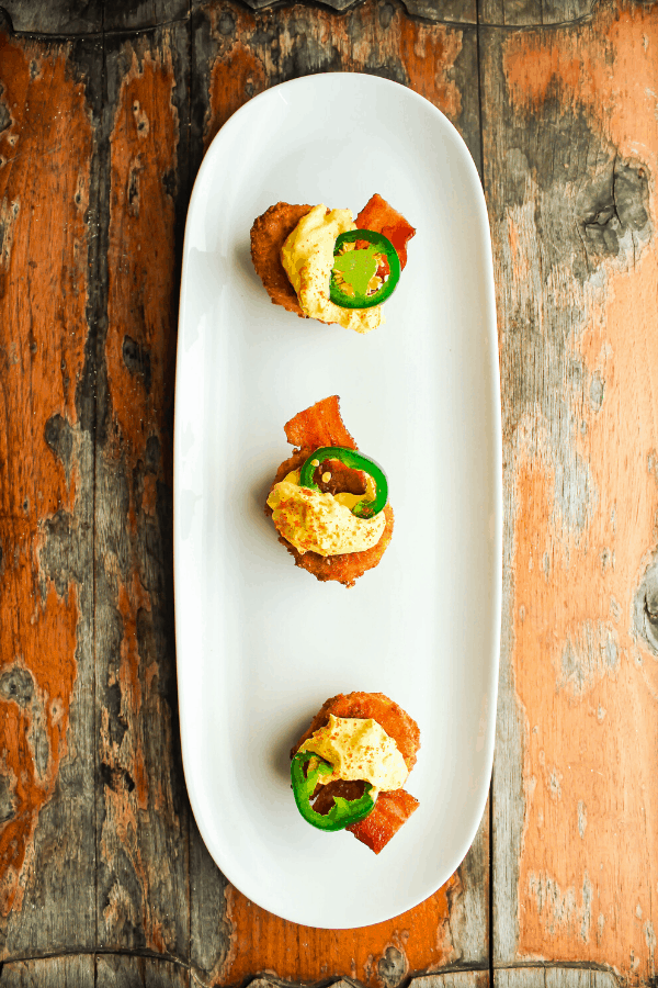 Three deep fried jalapeno popper deviled eggs on a white tray atop a distressed wood surface from above
