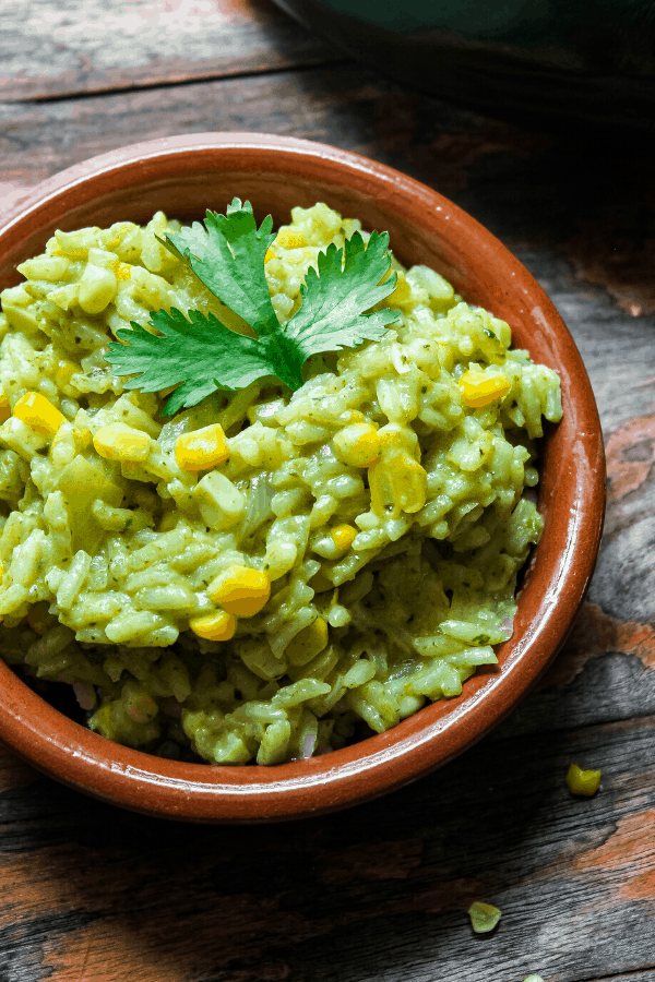 small bowl of creamy poblano rice w/ corn with sprig of cilantro on distressed table with corn kernels and poblano in background