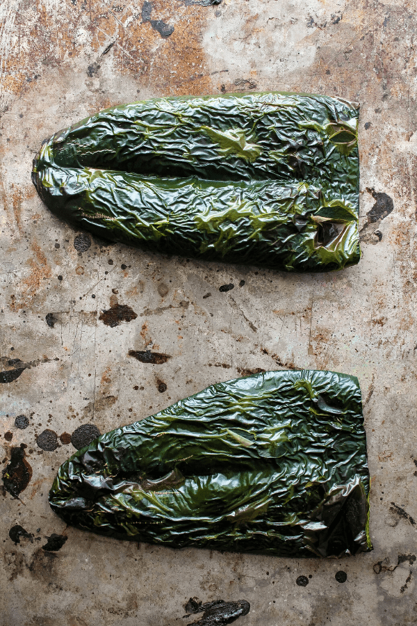 two roasted poblano slices on a baking sheet shot from above