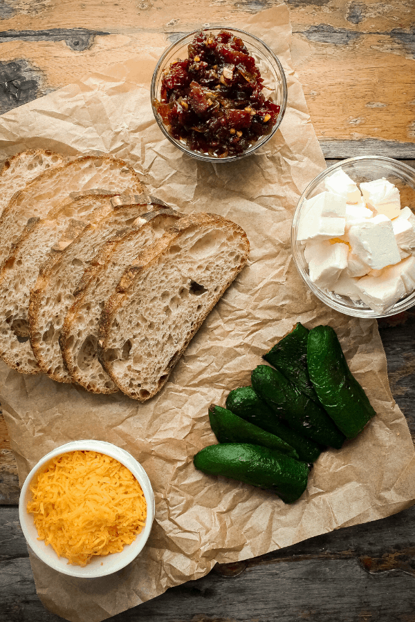 ingredients for jalapeno popper grilled cheese w/ bacon jam on distressed wood table from above