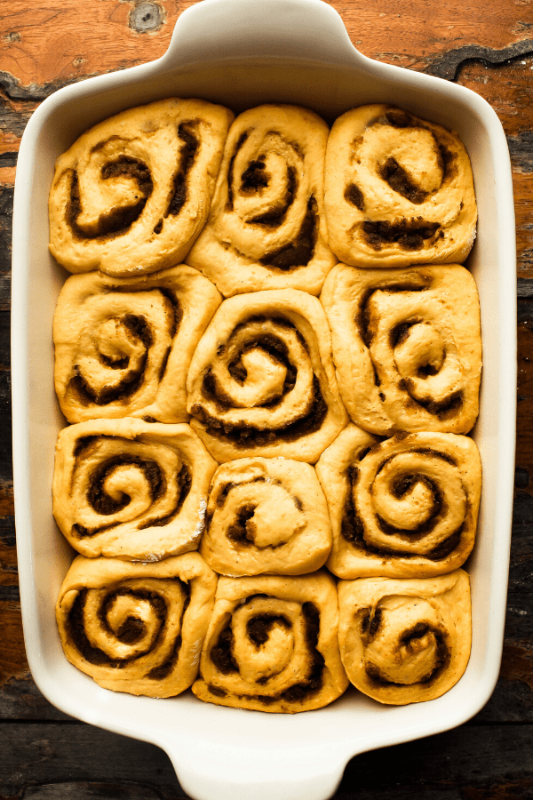 pumpkin cinnamon rolls with chai spice in pan after rising