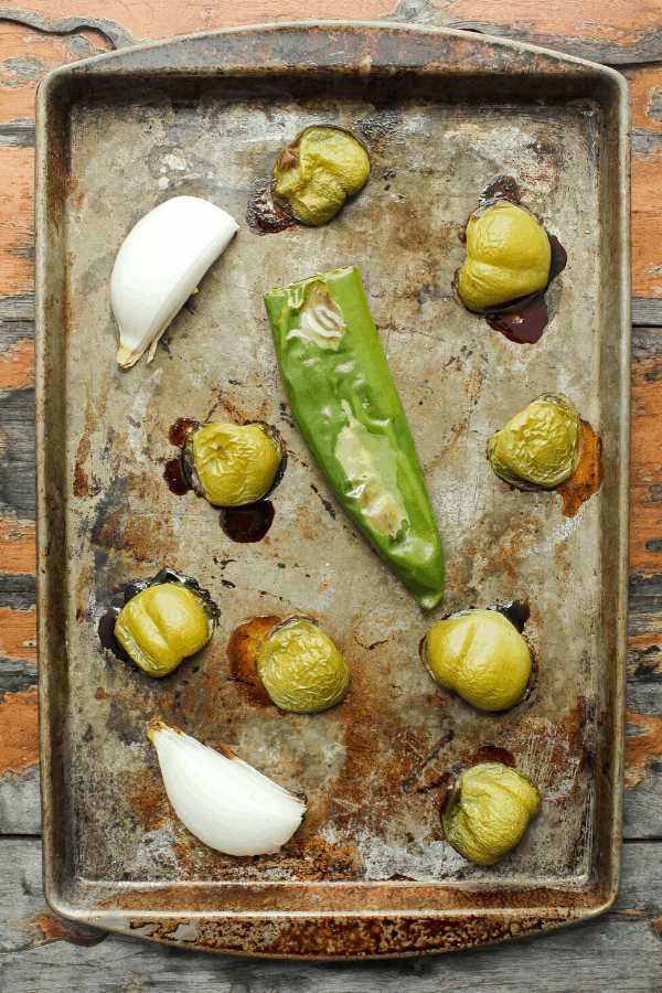 roasted tomatillos, onions, and Anaheim pepper on a baking sheet shot from above.
