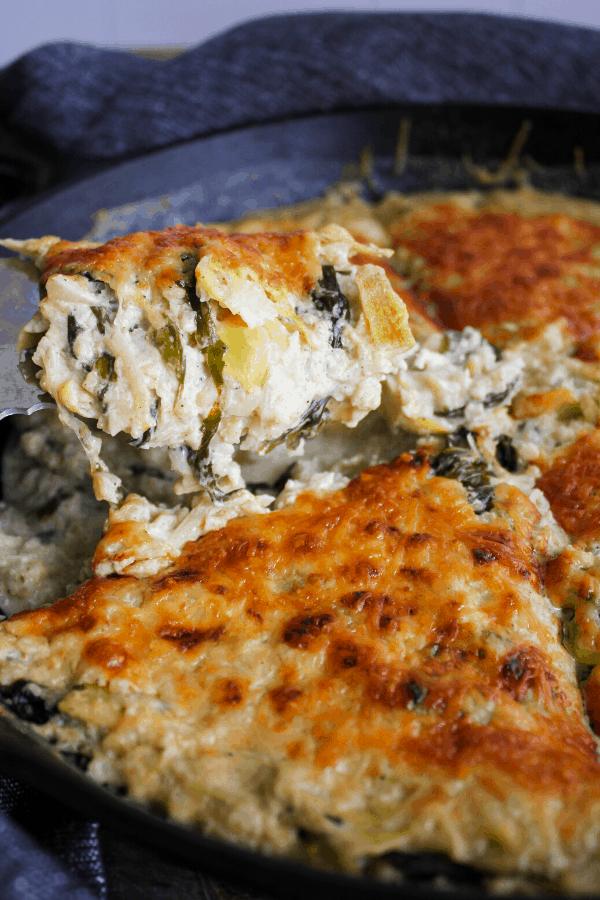 Spatula with slice of casserole above casserole in cast-iron skillet.
