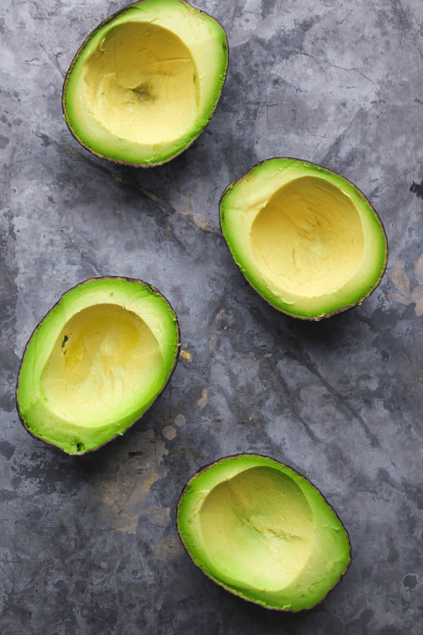 four pitted and scooped out avocado halves on a grey surface shot from above