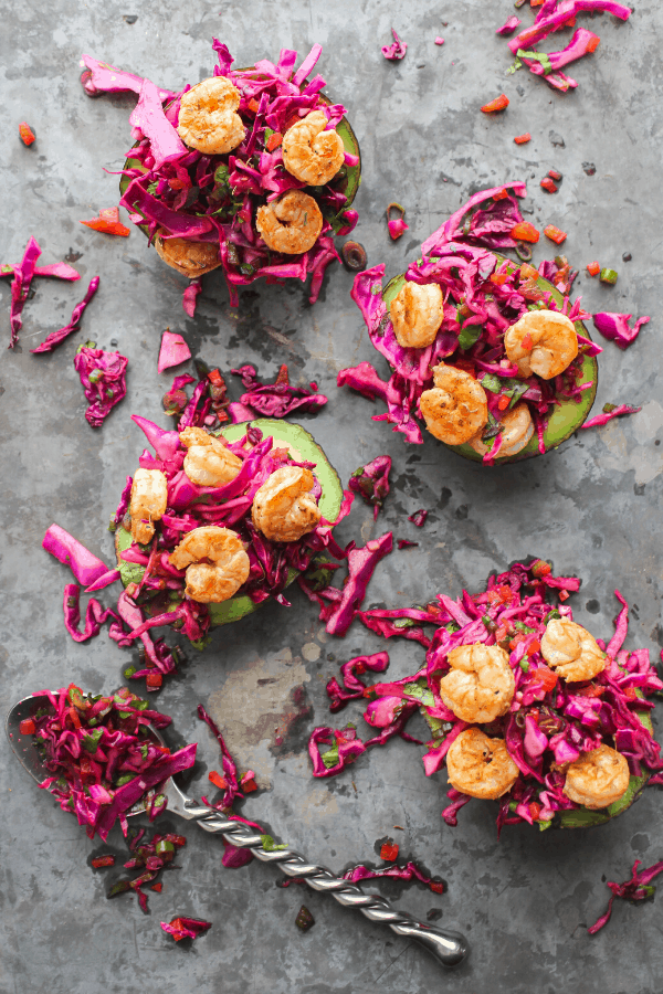 four Mexican slaw & shrimp stuffed avocados on a baking sheet with a spoon of slaw