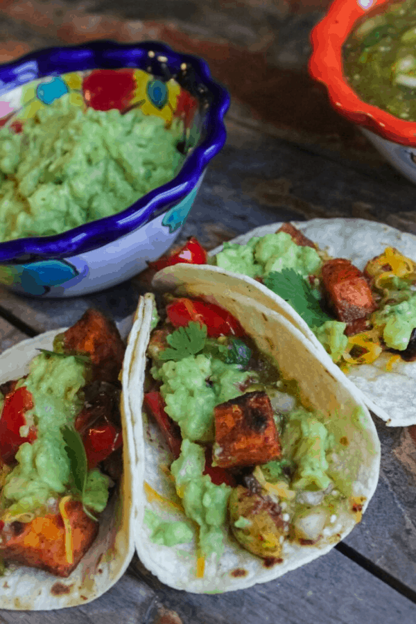 Three roasted vegetable tacos surrounding a small bowl of mashed avocado.