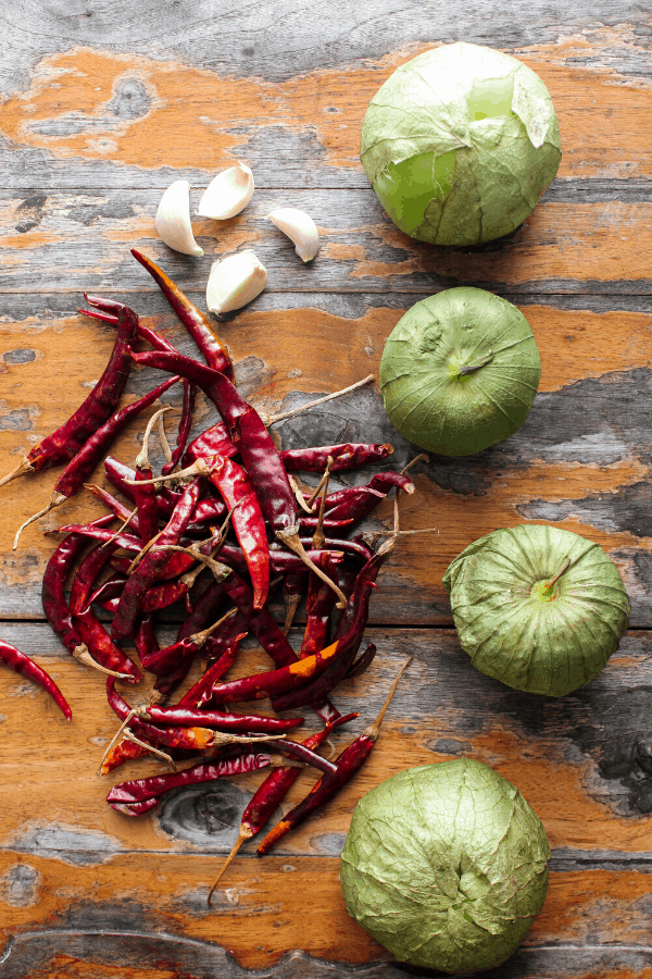 Four tomatillos, four garlic cloves, and pile of chile de árbol chiles on a distressed wood surface shot from above.