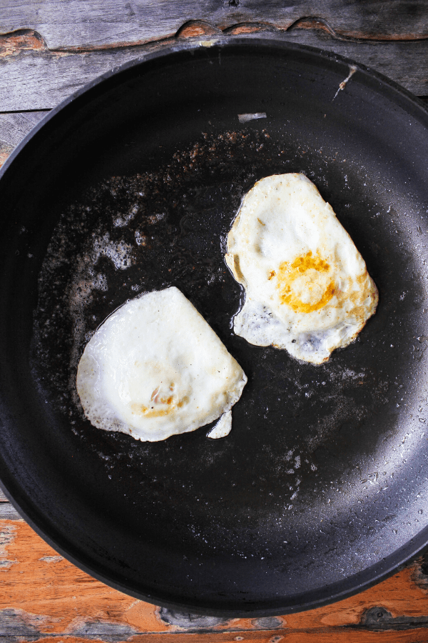 Two fried eggs in a skillet shot from above.