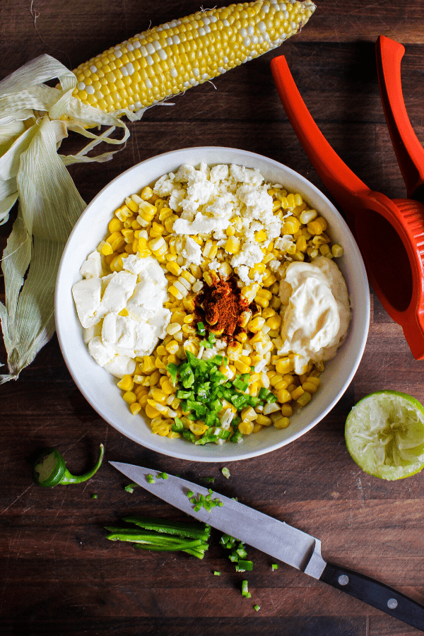 Mexican street corn ingredients in a white bowl with corn cob, juicer, lime, and diced jalapeno with knife on a wood surface shot from above.