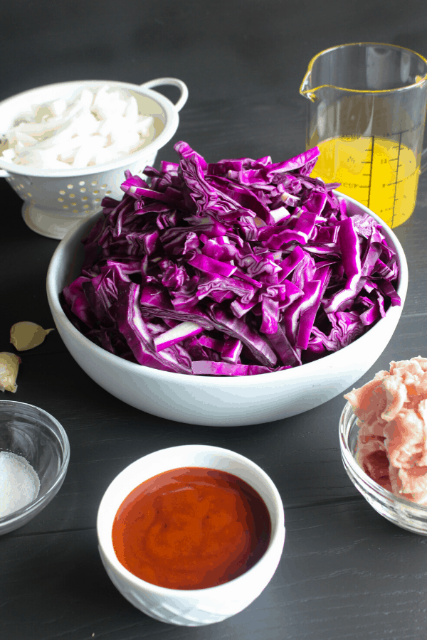 Ingredients for braised cabbage in bowls on a grey surface.