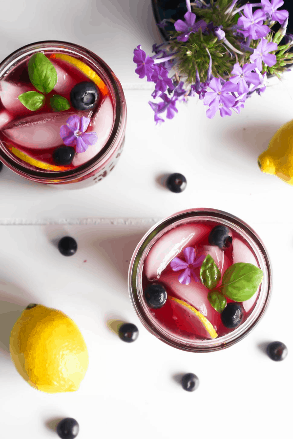 Top down shot of two jars of blueberry basil lemonade, vase of purple flowers, a lemon, and scattered blueberries.